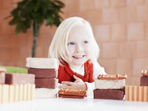 Young smiling girl with mini bricks and bare clay block wall in background